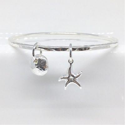 Kira Solid silver bangle with seaside charms. Handcrafted bangle with starfish and pebble charms