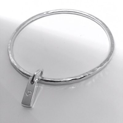 Silver hammered bangle with bar charm